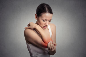 Joint inflammation indicated with red spot on females elbow. Arm pain and injury concept. Closeup portrait woman with painful elbow on gray background